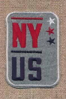 Grå motiv med teksten NY-US og stjerner