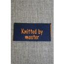 """Blå/orange mærke """"Knitted by moster"""""""